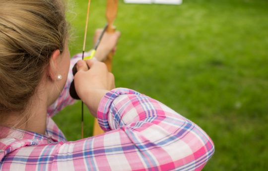 junge Frau zielt auf Zielscheibe mit Pfeil und Bogen