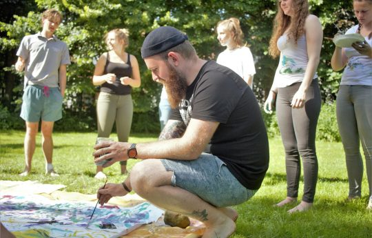 junger Mann kniet an großer Leinwand auf Wiese und malt mit Pinsel, weitere junge Menschen im Hintergrund