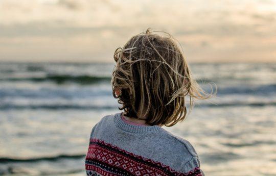 junge Person von hinten blickt auf Meer hinaus bei Sonnenaufgang