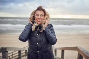 Lachende Frau mittleren Alters bei windigem Wetter am Strand