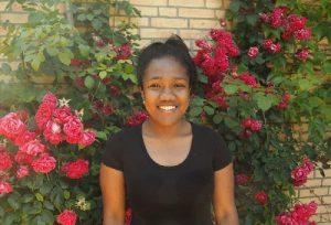 Portrait lächelnde junge Frau aus Madagaskar vor Rosenbusch