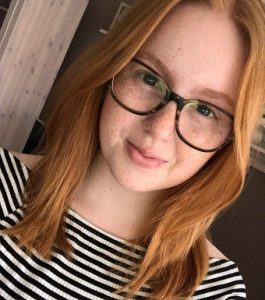 Portrait lächelnde junge Frau mit Brille, Sommersprossen und roten Haaren