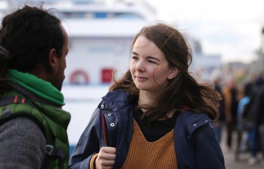 junge Frau mit Rucksack in einem Hafen im Gespräch mit einem jungen Mann