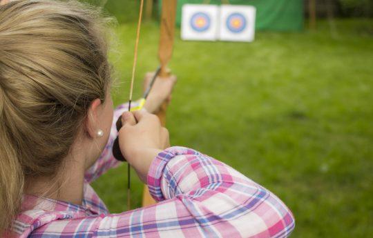 junge Frau, die mit Pfeil und Bogen auf eine Zielscheibe zielt